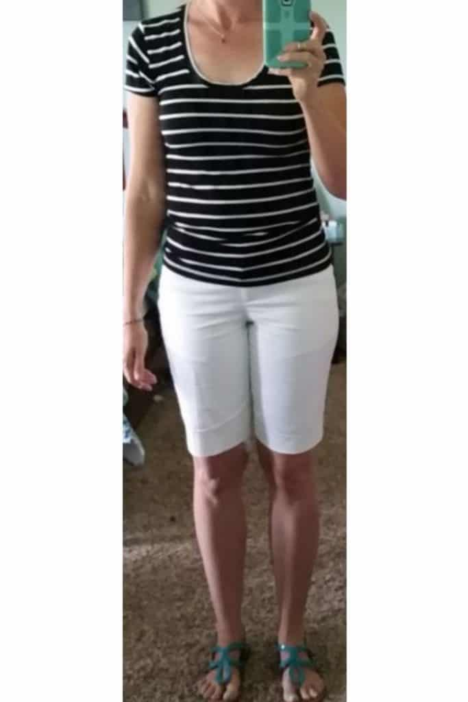April from Stunning Style wearing a black and white striped shirt and white Bermuda shorts.