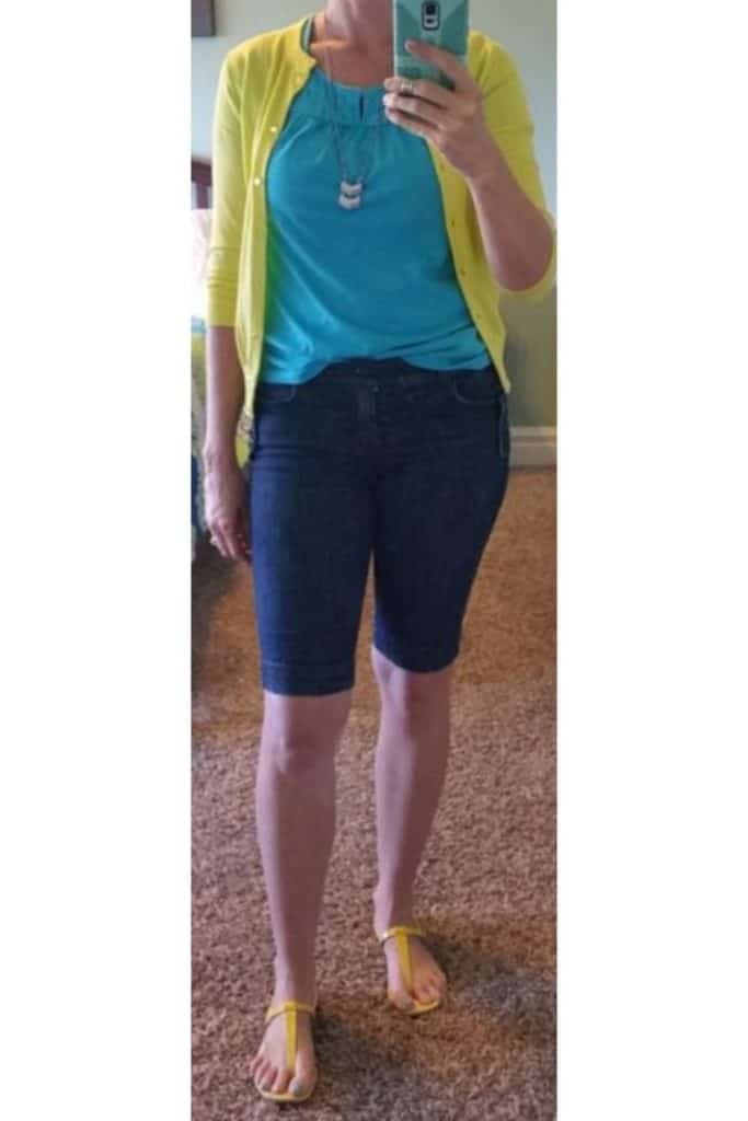 Yellow cardigan and sandals with cyan crochet top and navy Bermuda shorts.