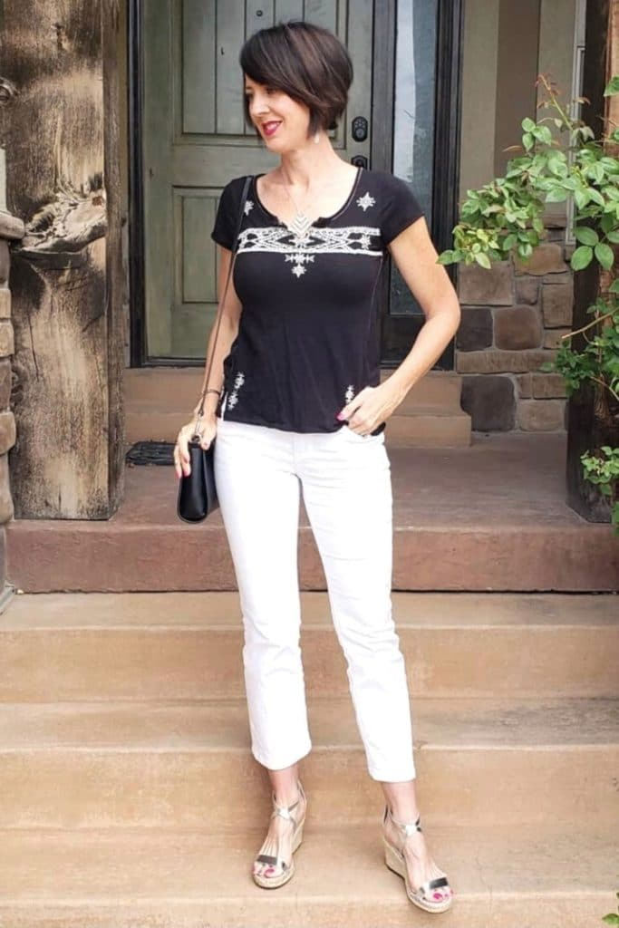April from Stunning Style wearing a black pattern shirt and white cropped pants.