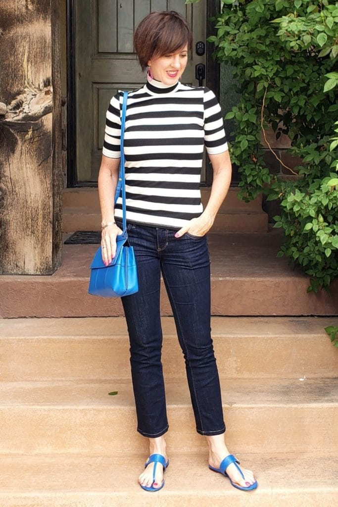 April from Stunning Style wearing a black and white striped turtleneck tee with black pants and blue accessories.