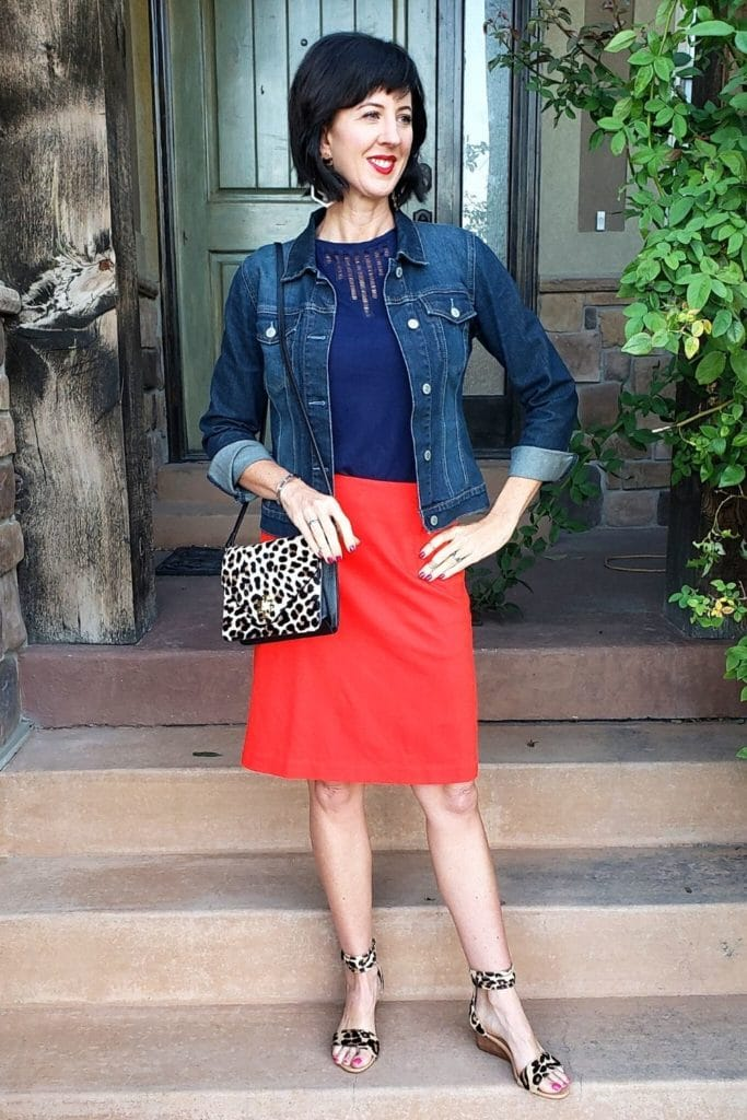 April from Stunning Style wearing a denim cropped jacket with a red skirt and leopard print accessories.