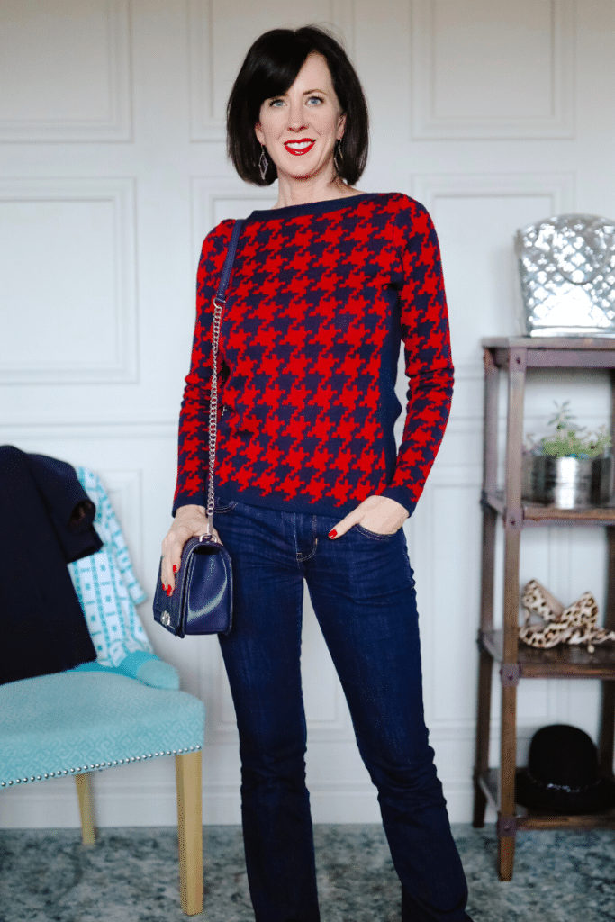 April from Stunning Style wearing a red and navy houndstooth sweater and blue jeans.