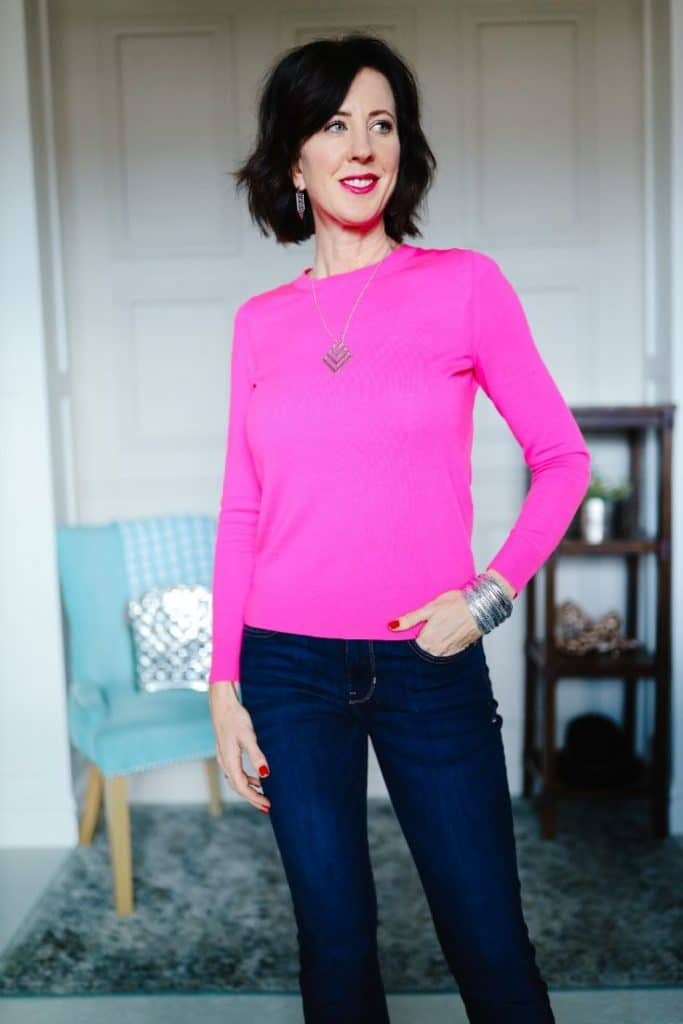 April from Stunning Style wearing a pink knit top and dark wash jeans.