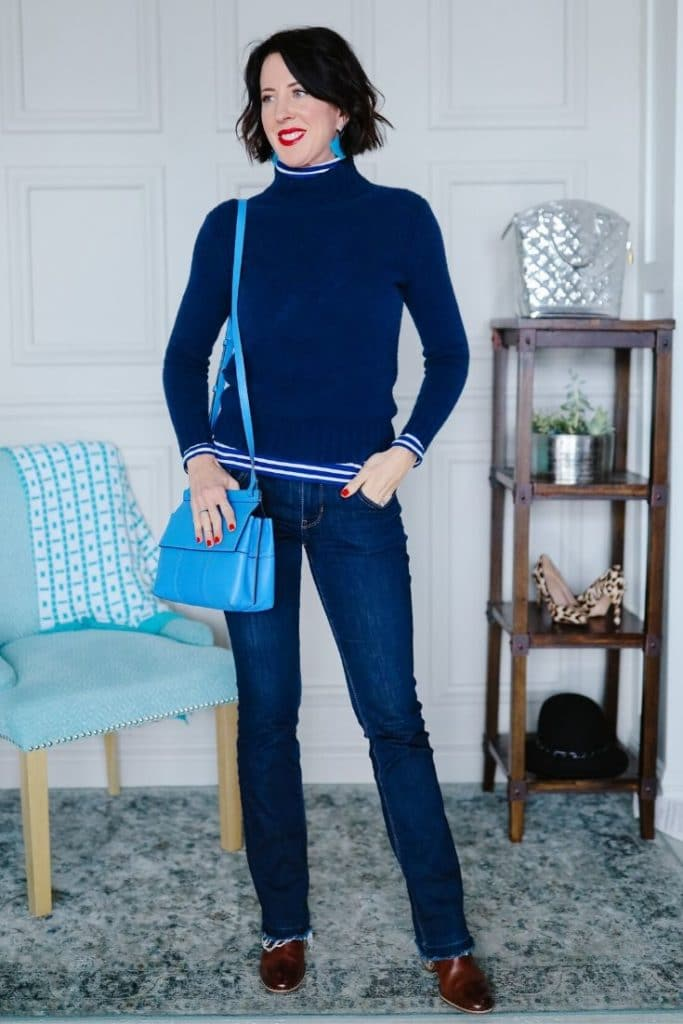 April from Stunning Style wearing a navy top with dark wash jeans and a light blue bag.