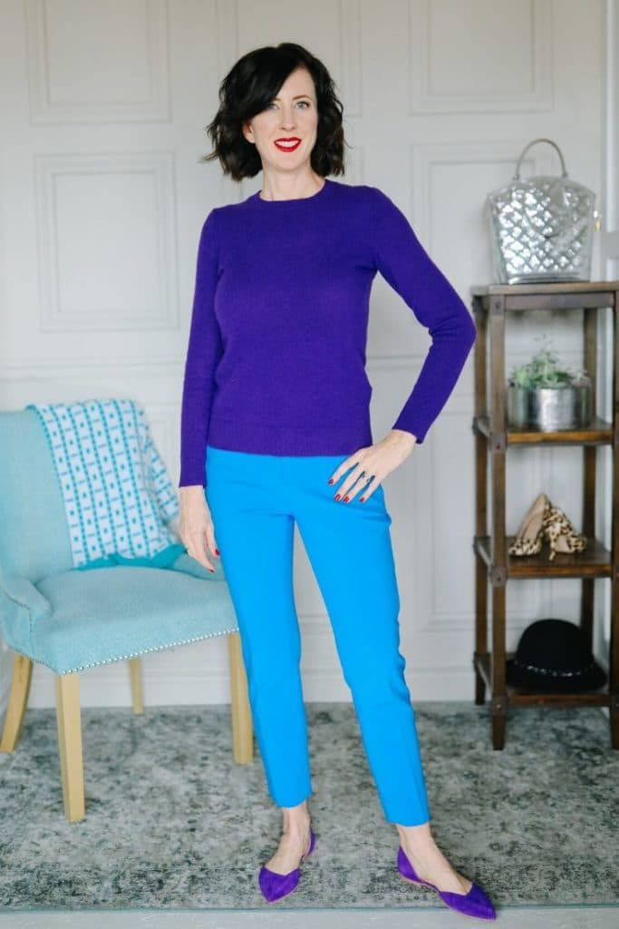 April from Stunning Style wearing a purple top with blue pants and purple flats.
