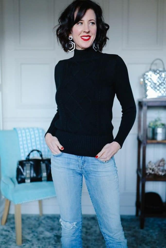 April from Stunning Style wearing a black turtleneck sweater and light wash jeans.