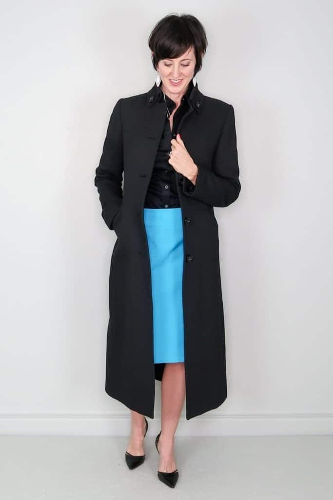 April from Stunning Style showing off her affordable wardrobe by wearing a long black wool coat and blue skirt.