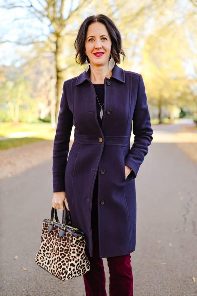 April from Stunning Style showing off her affordable wardrobe by wearing a navy coat with leopard print bag.