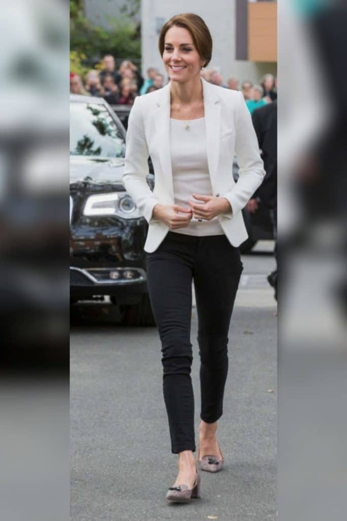 Kate Middleton wearing dark skinny pants with a white blazer.
