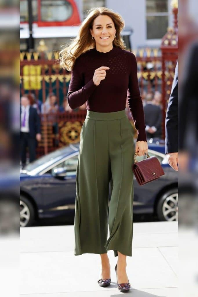Kate Middleton wearing dark green wide-leg trousers and a fitted top.