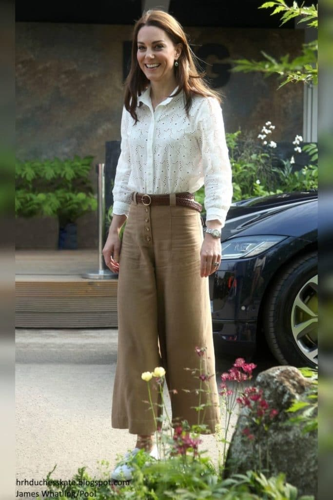Kate Middleton wearing tan wide-leg trousers with a white linen blouse.