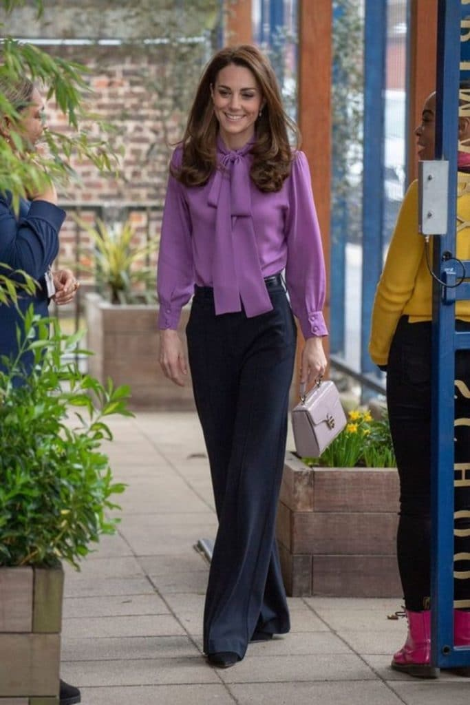 Kate Middleton wearing a soft knit top with navy wide-leg trousers.