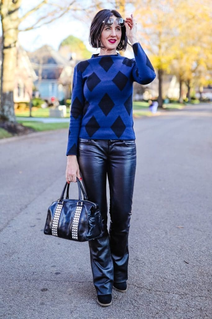 April from Stunning Style showing off her signature edgy classic style by wearing leather pants, leather bag and bold pattern top.