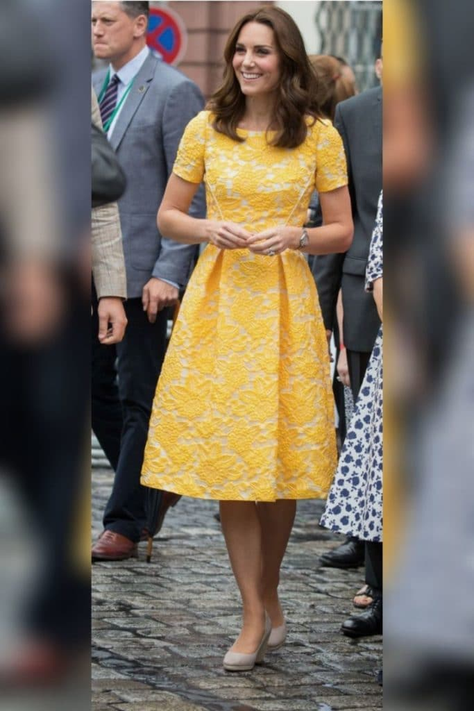 Kate Middleton wearing a yellow fit and flare dress with nude heels.