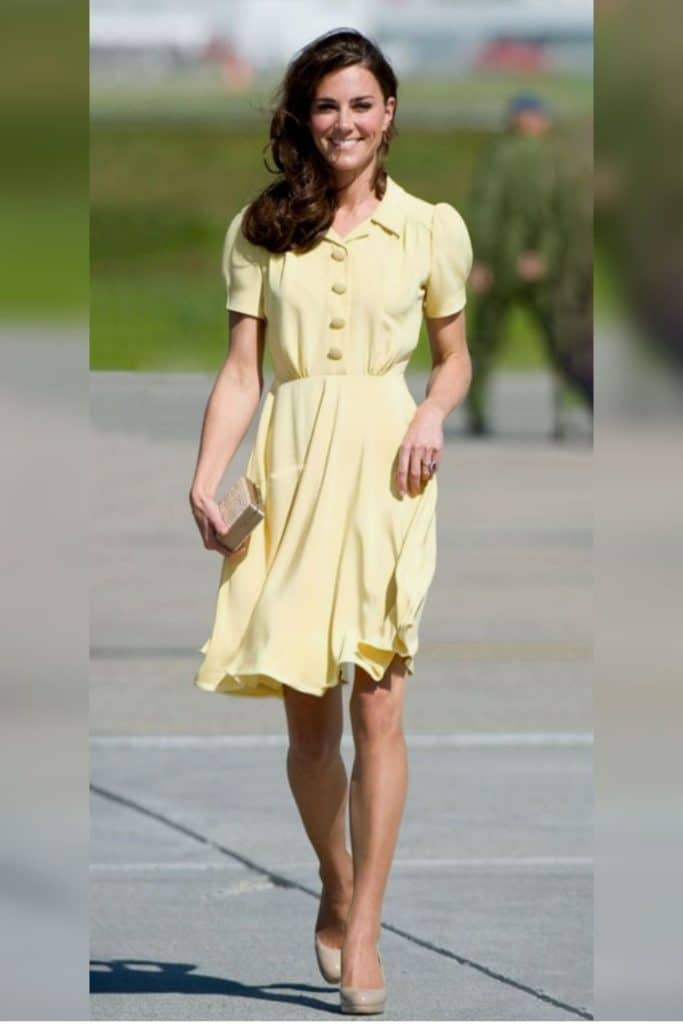 Kate Middleton wearing a yellow fit and flare dress with puff sleeves.