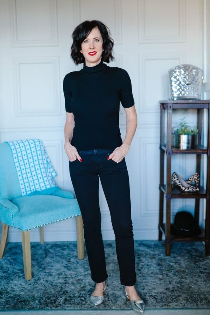 April from Stunning Style showing her signature style by wearing a black turtleneck with dark wash jeans.