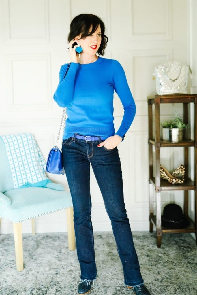 April from Stunning Style showing her signature style by wearing a blue sweater with jeans.