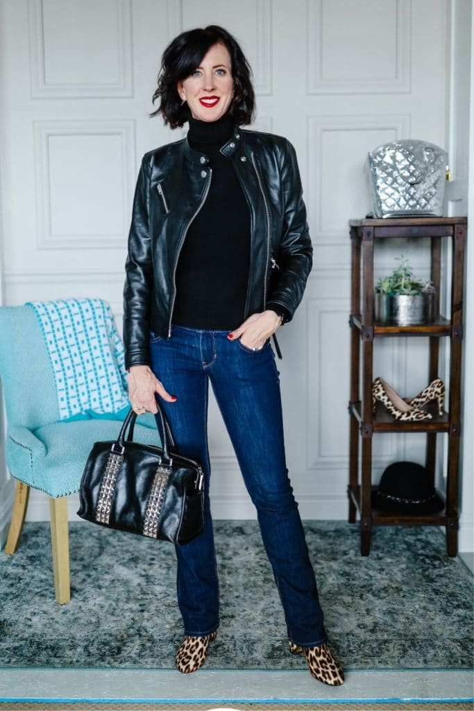 April from Stunning Style showing her signature style by wearing a leather jacket with black turtleneck and jeans.