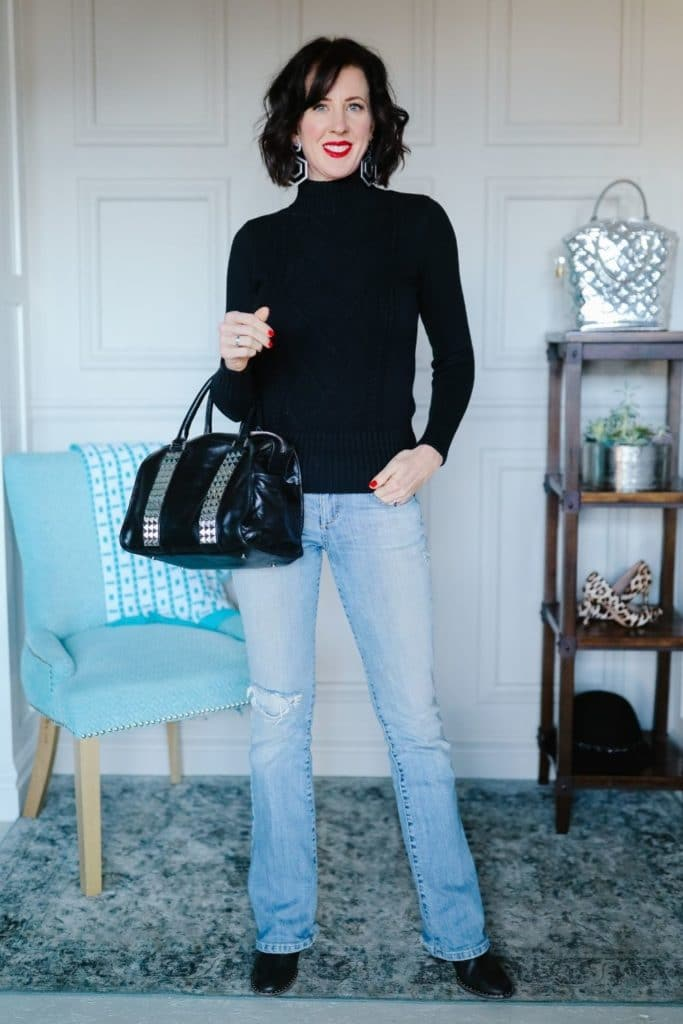 April from Stunning Style showing her signature style by wearing a black turtleneck with light wash jeans.
