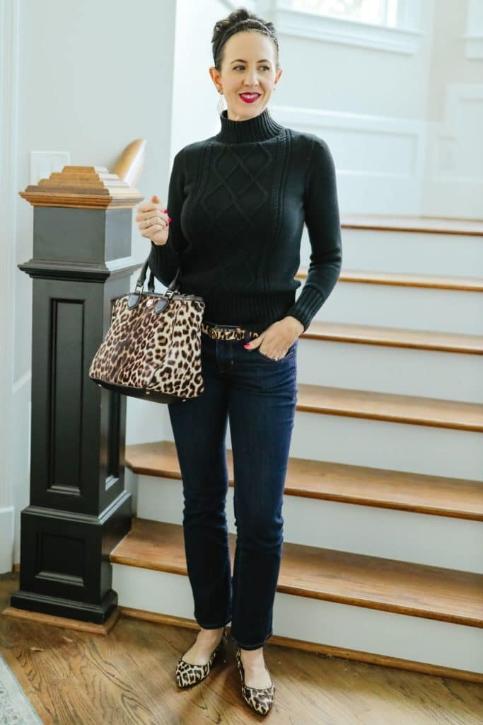 April from Stunning Style showing her signature style by wearing a black turtleneck sweater, jeans and matching leopard accessories.