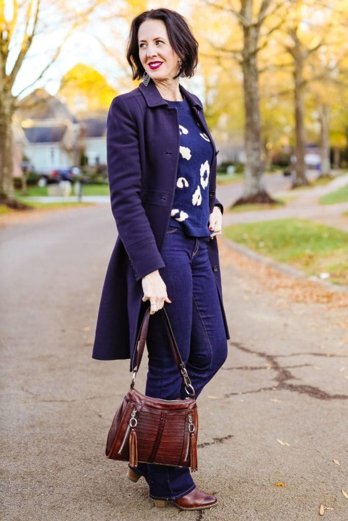 April from Stunning Style showing her signature style by wearing a black coat, jeans, and patterned sweater.