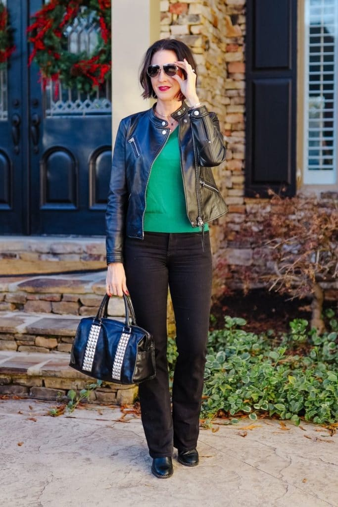 April from Stunning Style showing her signature style by wearing a leather jacket, green sweater and black pants.