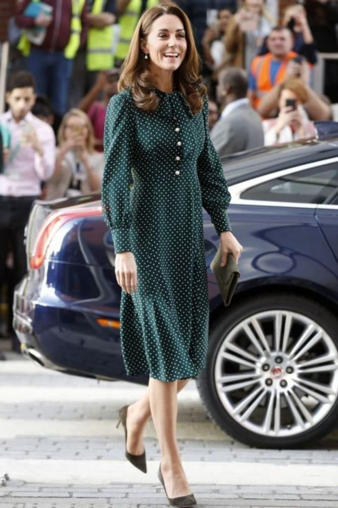 Kate Middleton wearing a dark green fit and flare dress with leg of mutton sleeves.