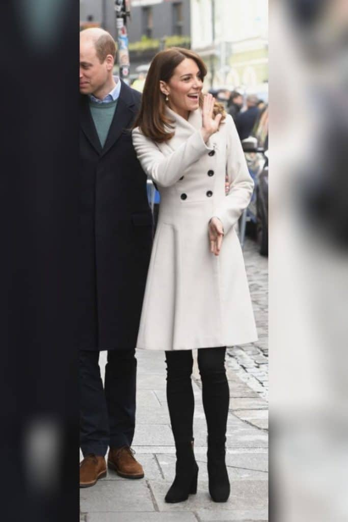 Kate Middleton wearing a long white blazer coat.