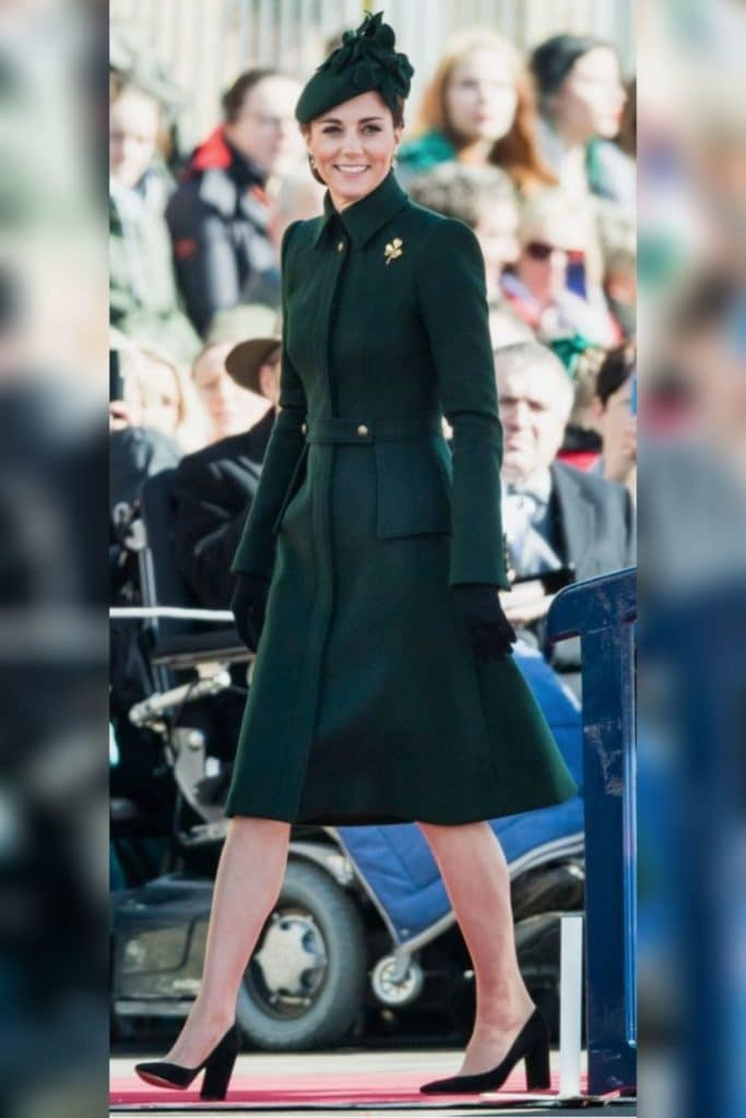 Kate Middleton wearing a dark green coat and embellished hat.