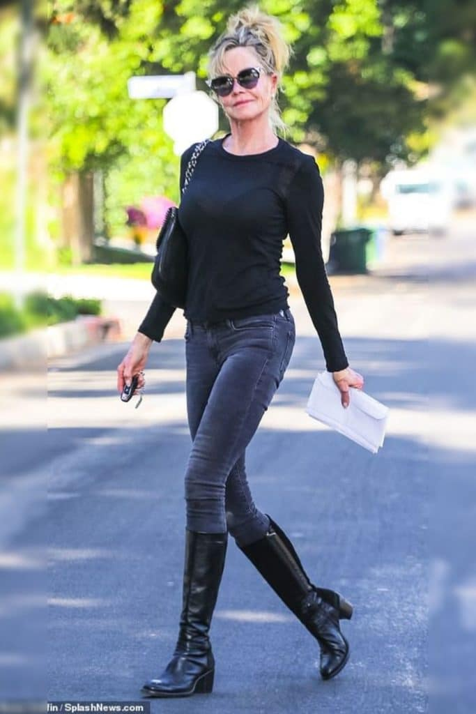 Melanie Griffith wearing a black top and jeans.
