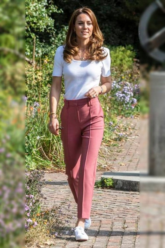 Kate Middleton wearing a white top and red pants.