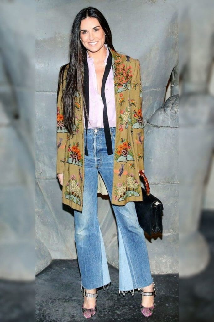 Demi Moore wearing a floral patterned cardigan and jeans.