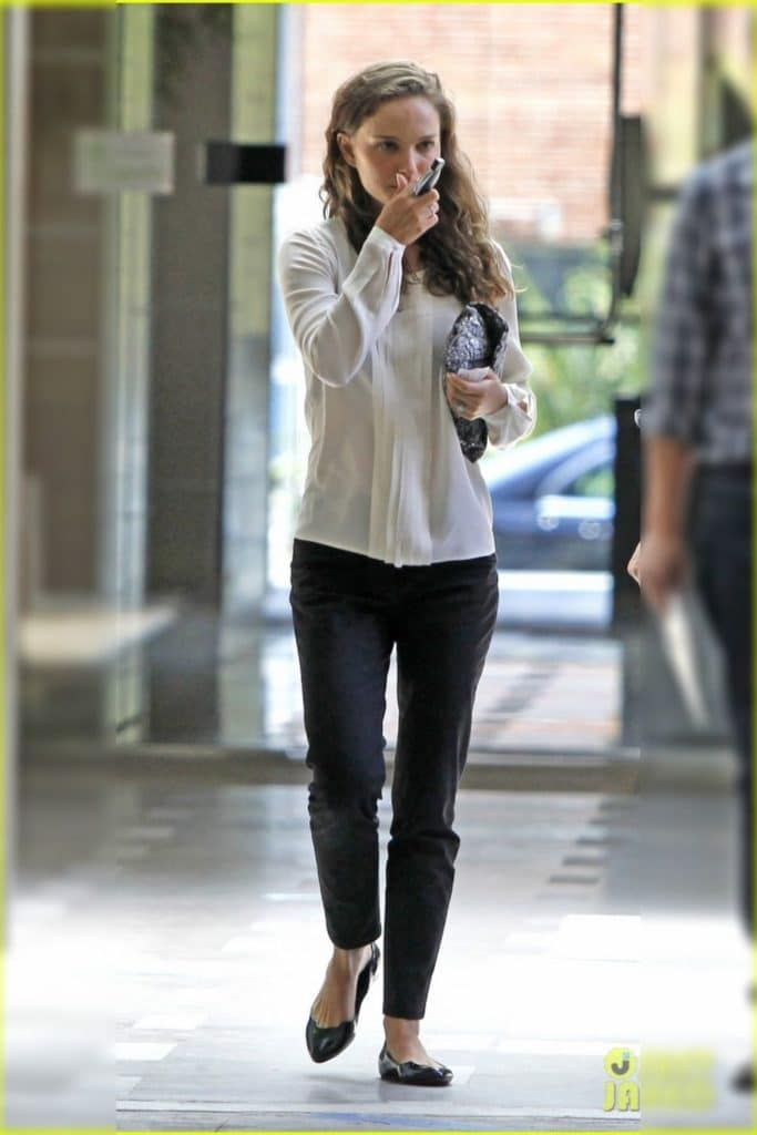 Natalie Portman wearing a white blouse and jeans.