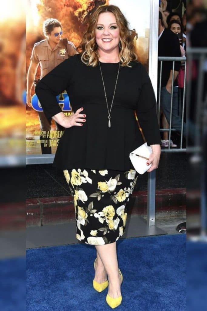 Melissa McCarthy wearing a floral skirt and black top.