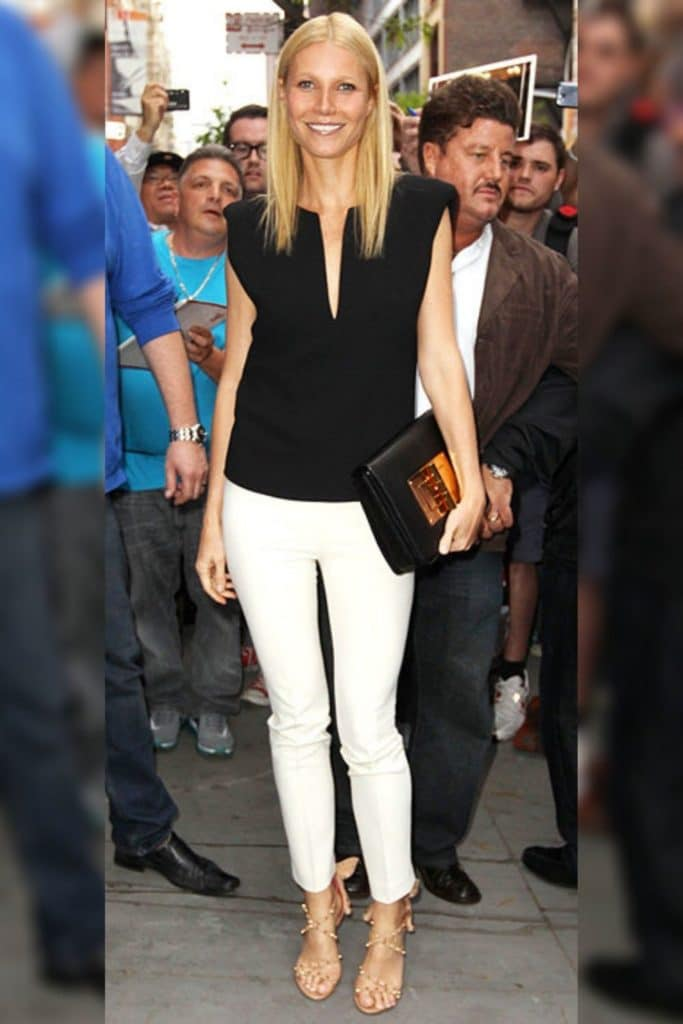 Gwyneth Paltrow wearing a black top with white pants.