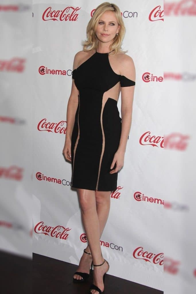 Charlize Theron wearing a black dress.
