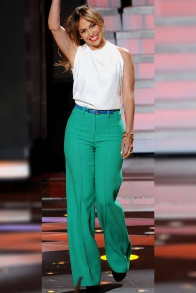 Jennifer Lopez wearing a white top and green pants.