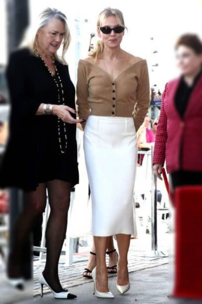 Renée Zellweger wearing a beige top and white skirt.