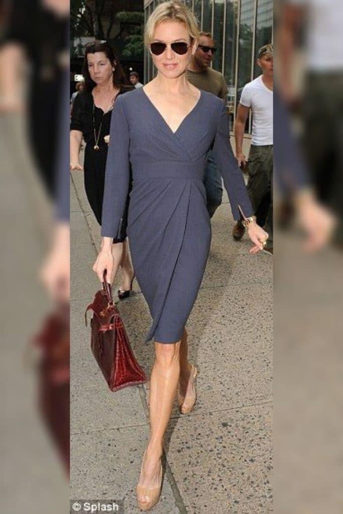Renée Zellweger wearing a navy dress.