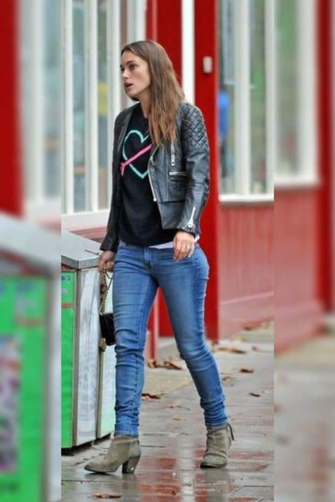 Keira Knightley wearing a black jacket, t-shirt and jeans.