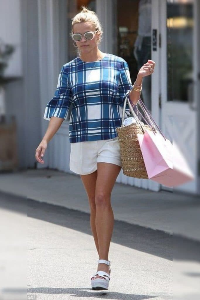 Reese Witherspoon wearing a straight fit top and shorts.