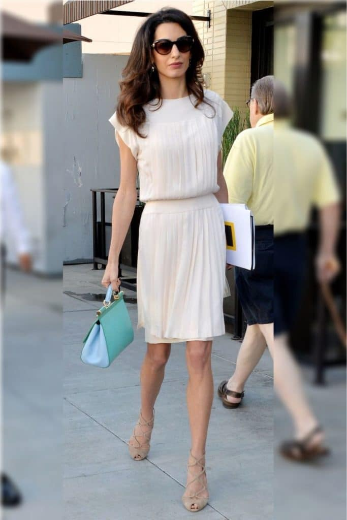 Amal Clooney wearing a cream dress.