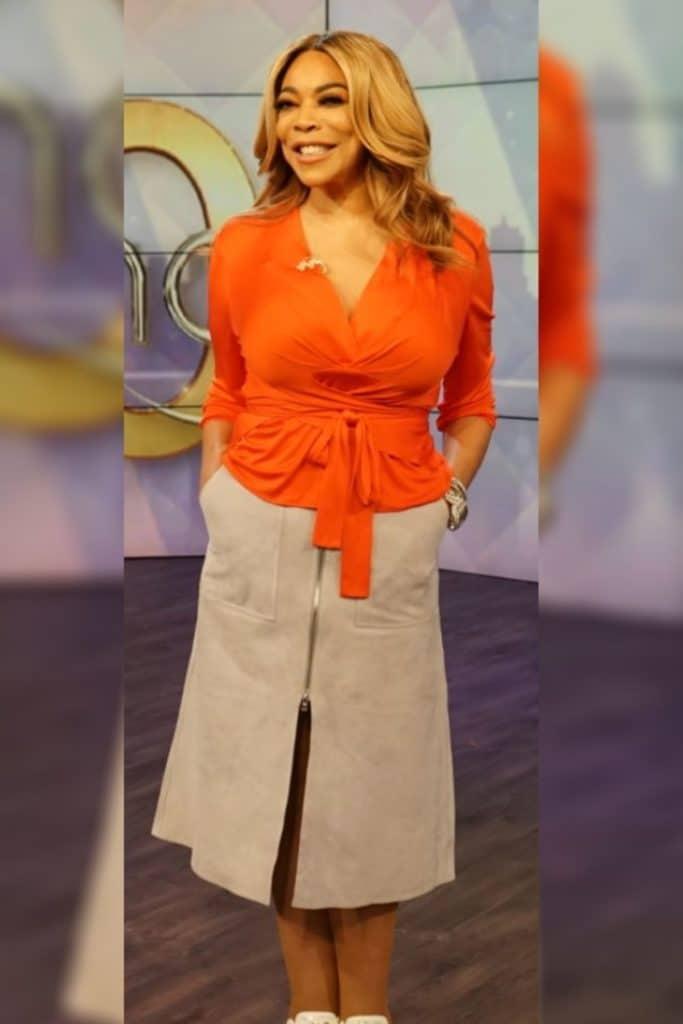 Wendy Williams wearing an orange top and tan skirt.
