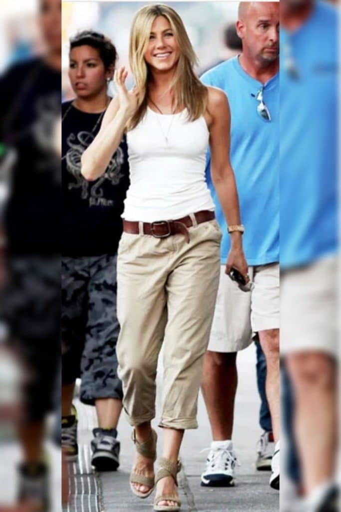 Jennifer Anniston wearing tan pants and a white top.