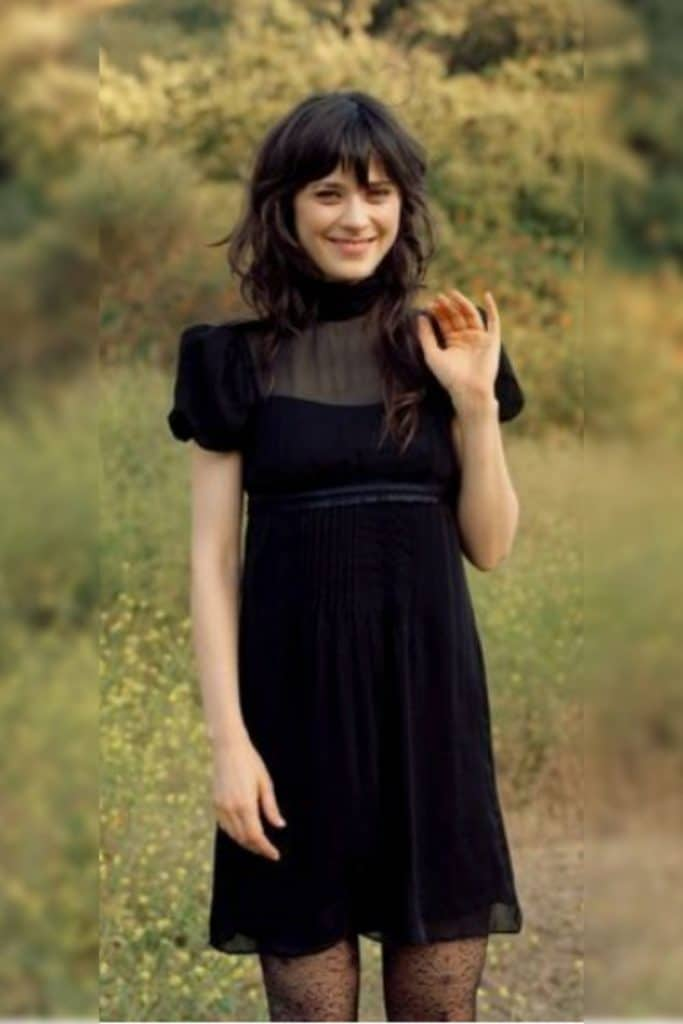 Zooey Deschanel wearing a black dress with puff sleeves.