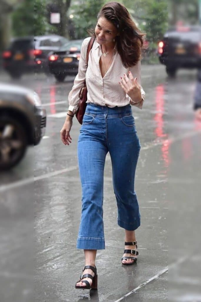 Katie Holmes wearing a cream button down top and jeans.