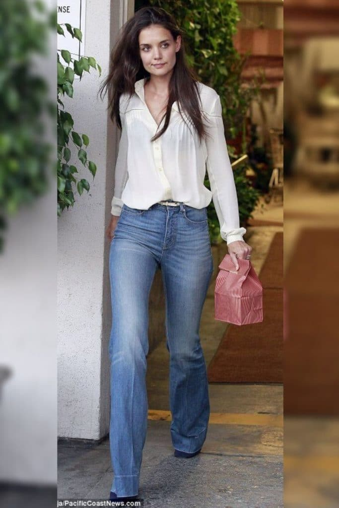 Katie Holmes wearing a white blouse and jeans.