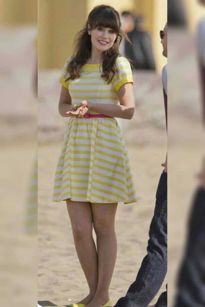 Zooey Deschanel wearing a yellow and white striped dress with puff sleeves.