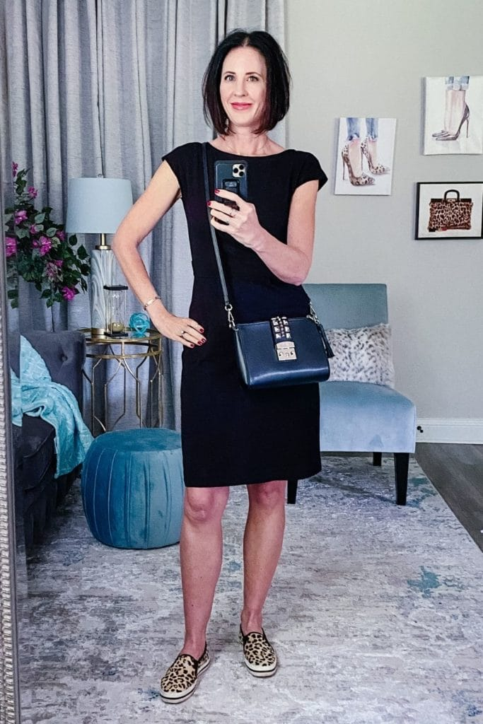 April from Stunning Style wearing a black dress with leopard sneakers and a navy cross body bag.