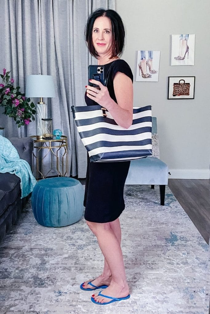 April from Stunning Style wearing a light dress with blue flip flops and a striped canvas bag.